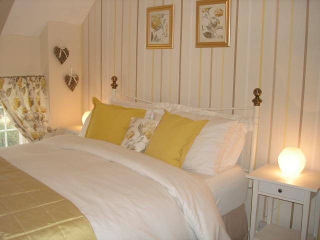 Bedroom 2 dressed with Laura Ashley soft furnishings, kingsize bed, dressing table & wardrobe