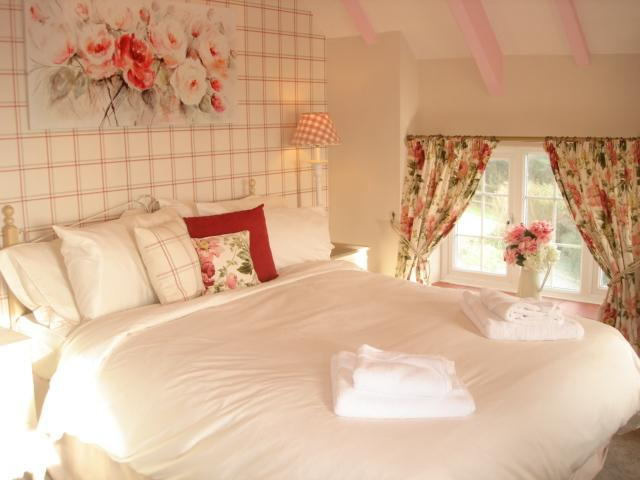 Master bedroom with Laura Ashley décor, kingsize bed where you can enjoy the sea view whilst in bed