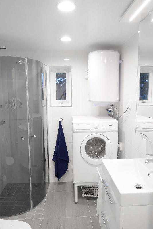 Bathroom with shower, washing machine / tumble dryer.