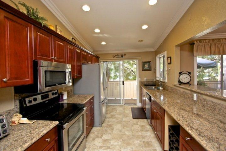 Highly upgraded kitchen with cherry cabinetry, granite counters, and stainless appliances