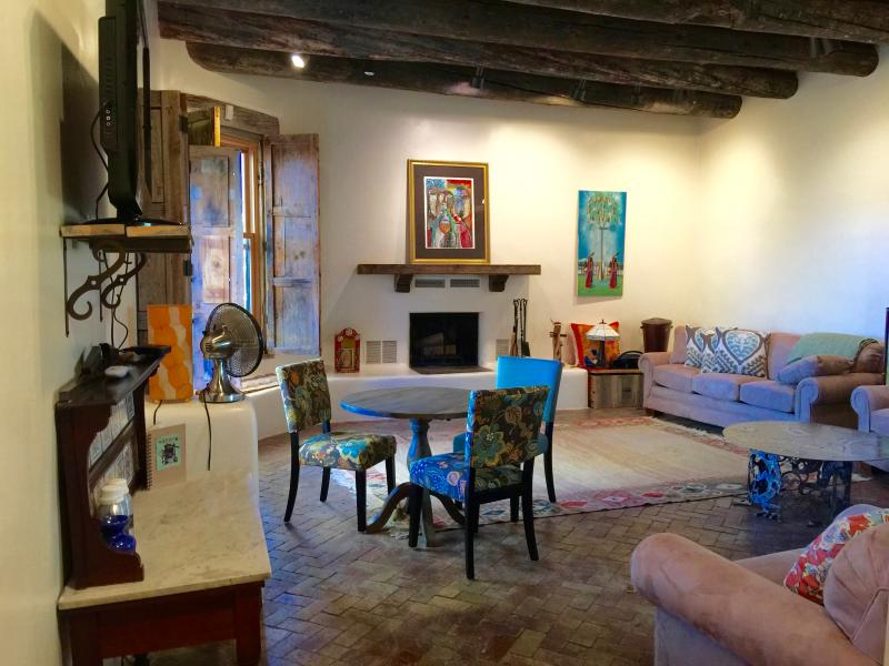 The living room is spacious, big fireplace, beams, traditional adobe.