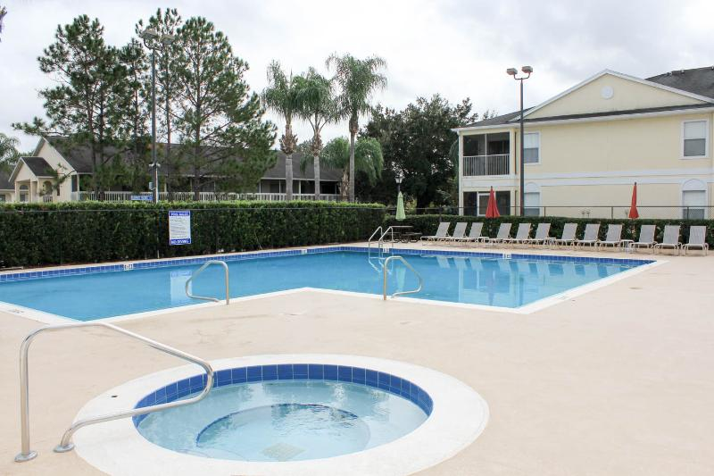 Large heated pool, hot tub and plenty of seating located just outside of unit
