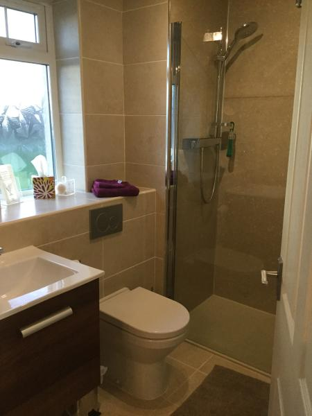 Fully tiled walk in shower with heated towel rail and underfloor heating.