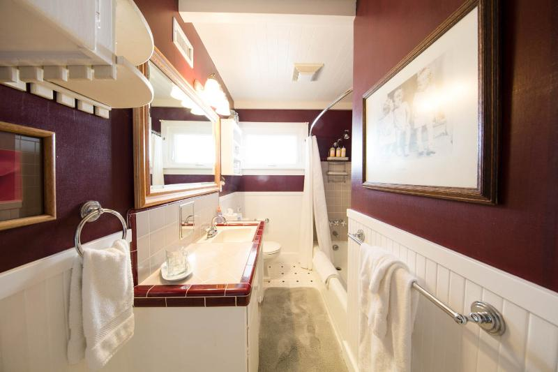 Updated bath with original tiles.  Tub and Shower. All Towels and linens are provided.