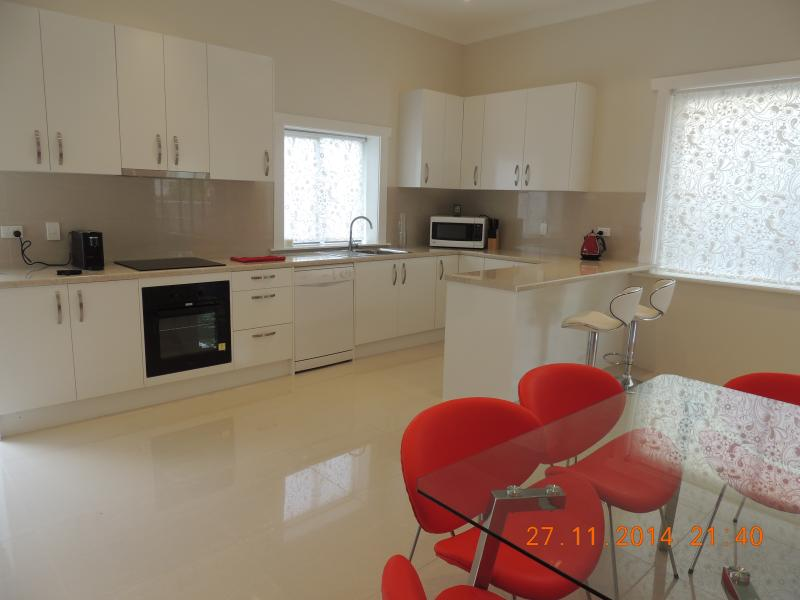 A modern kitchen with dishwasher, microwave, coffee machine, oven, hob, dining table and chairs.