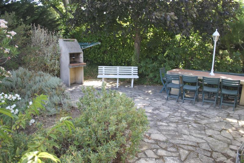 The patio at the back of La Florette, with barbecue, table and chairs.