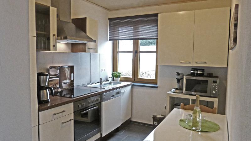 Küche mit Spülmaschine, Ceranfeld, Backofen, Kühlschrank mit Gefrierfach und kleinem Essbereich