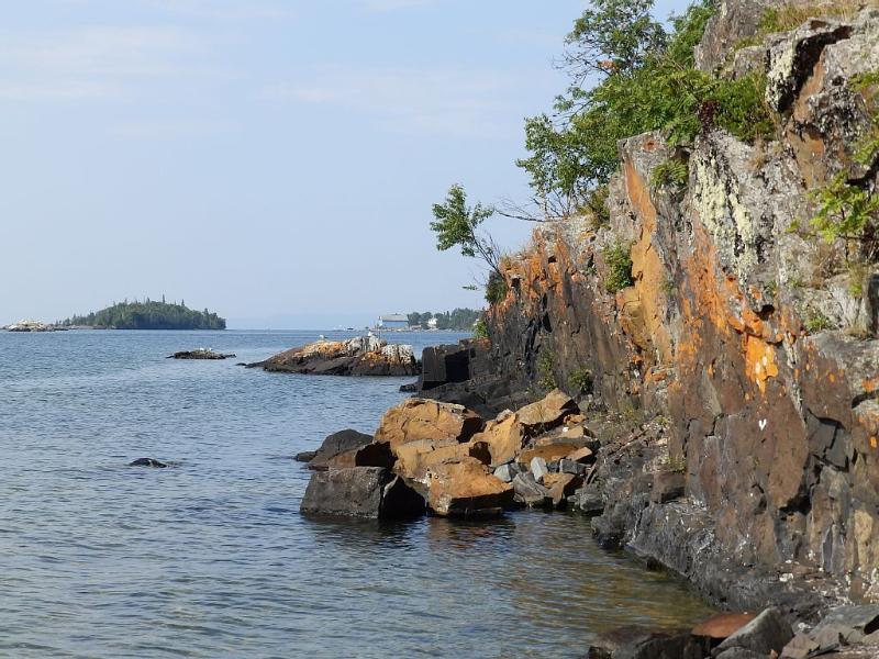 Opinión del acantilado de lado campamento de la Bahía de la propiedad con vistas al islote de plata tienda y la isla quemada.