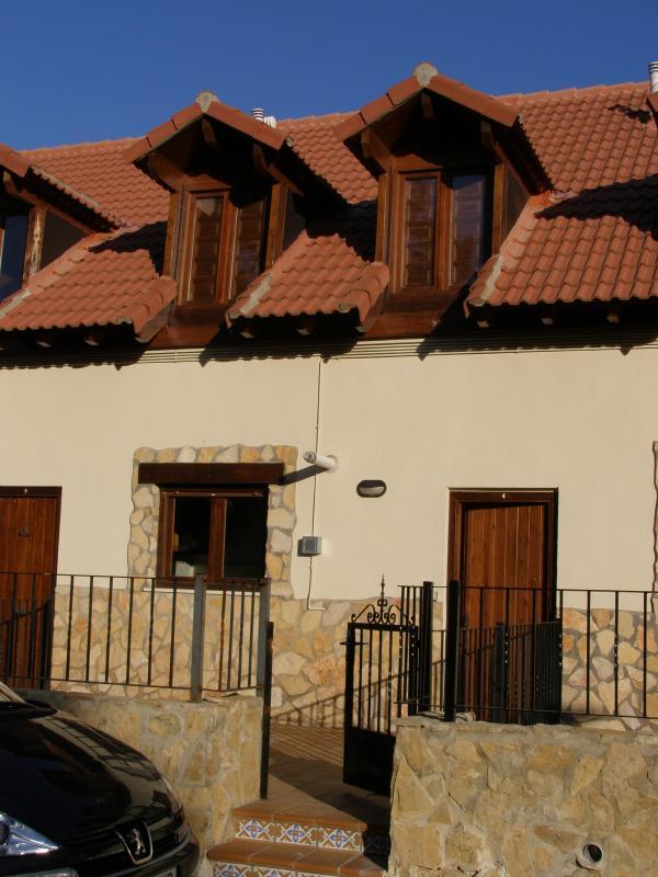 Fachada delantera con terraza propia y verjita que da a calle particular frente a un río y montaña.