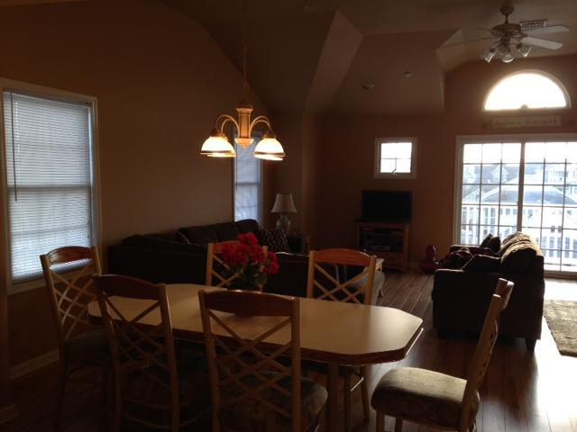 A view of part of the dining area and the living room. The space is light and airy. (Need new photo)