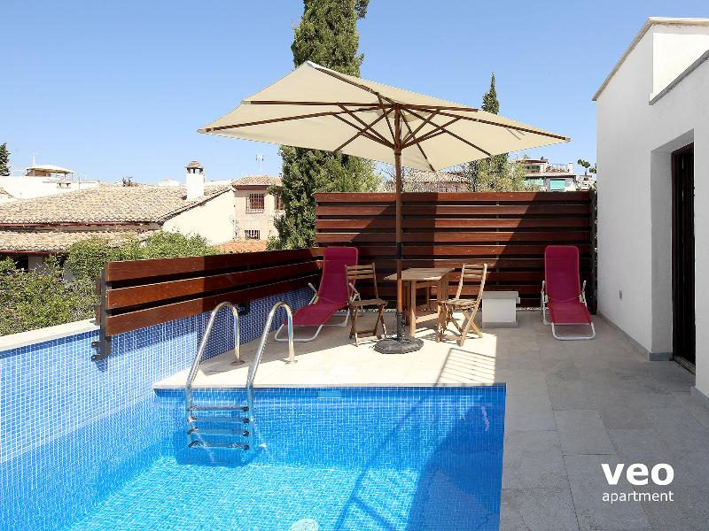 Terrace pool furnished with table, chairs, parasol and 2 deck-chairs.