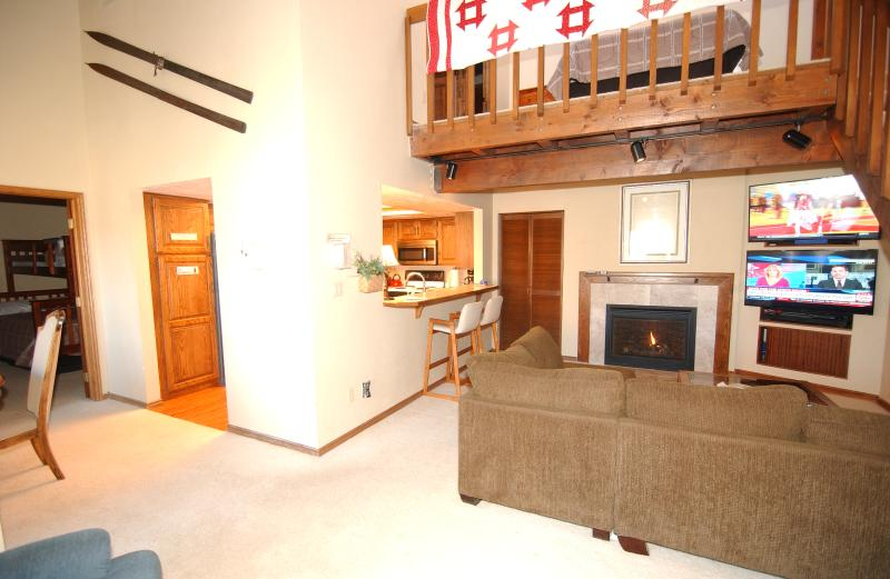 Entry area showing living room with natural gas fireplace,  large couch, Dual TV entertainment wall.