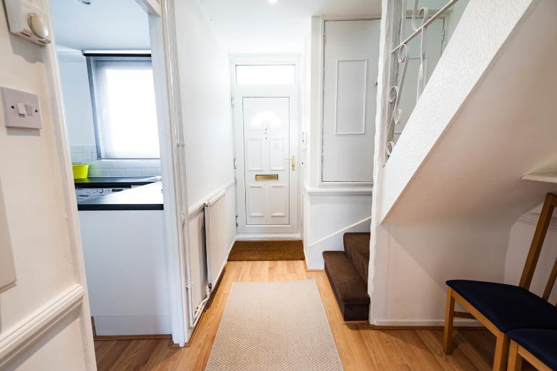 Entrance foyer looking towards the front door, with stairs leading upstairs to the three bedrooms