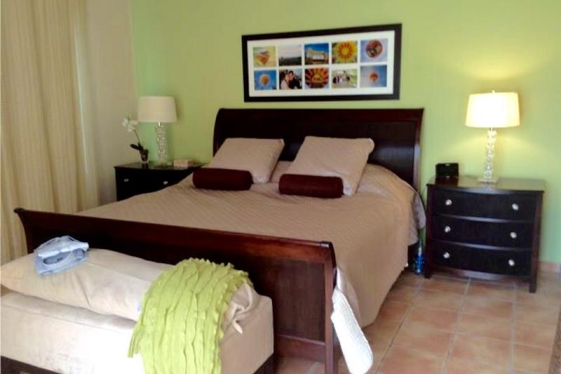 Master bedroom with king size bed, night tables and lamps