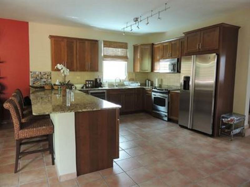 kitchen with granite countertop, seating with 4 stools and stainless steel appliances