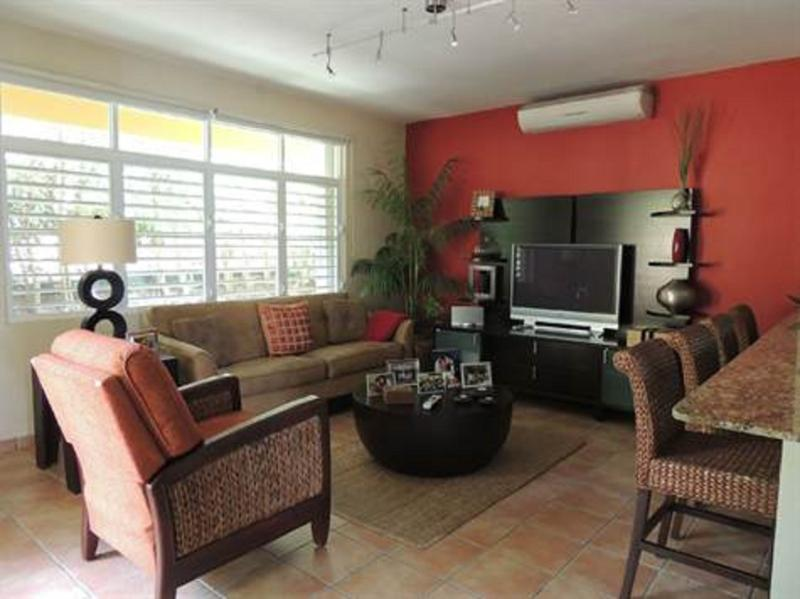 Living room with 42 inch TV, AC, sofas, tables and lamp nicely decorated with access to kitchen
