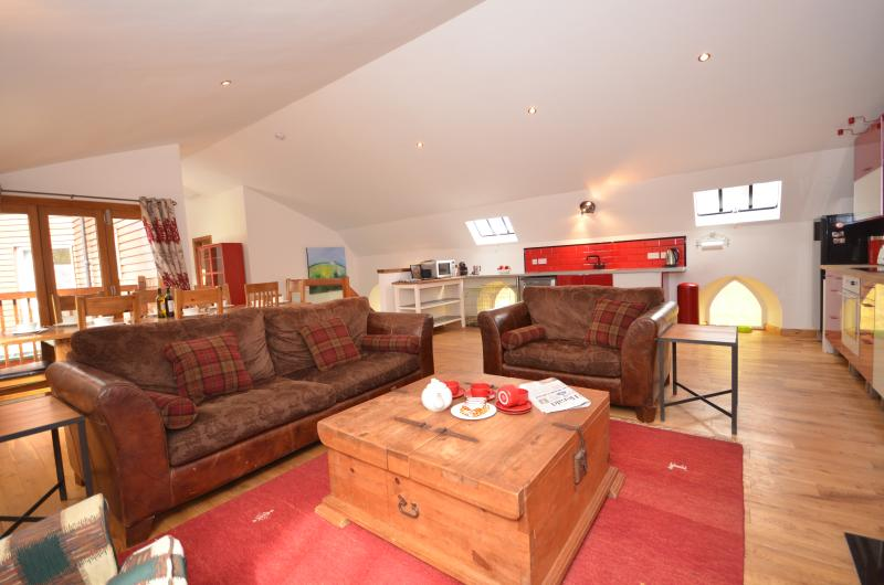 Bright spacious living area with fitted kitchen, stove, dining table and balcony