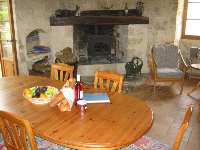 Welcome to the cosy dining room and its fireplace in the kitchen, opening on the garden