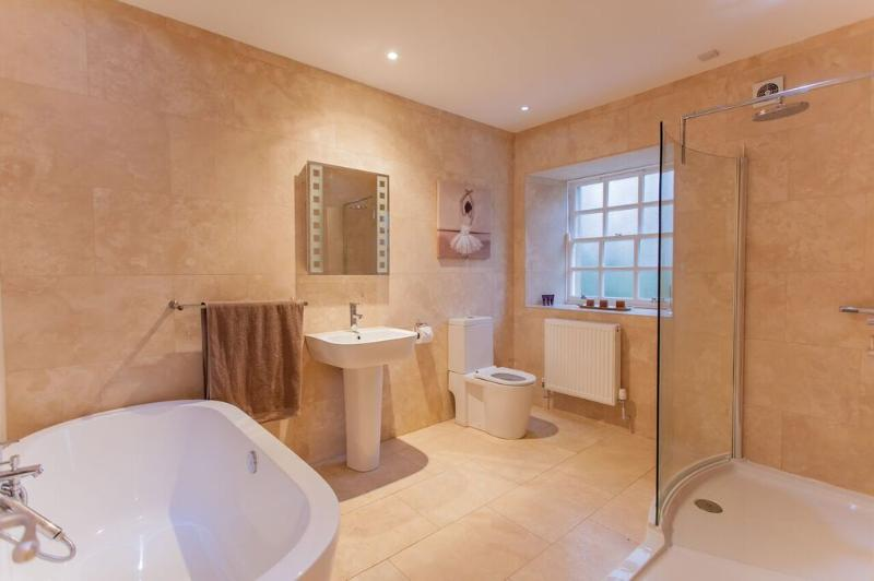Luxury bathroom with deep bath and double shower. Toiletries and towels included.