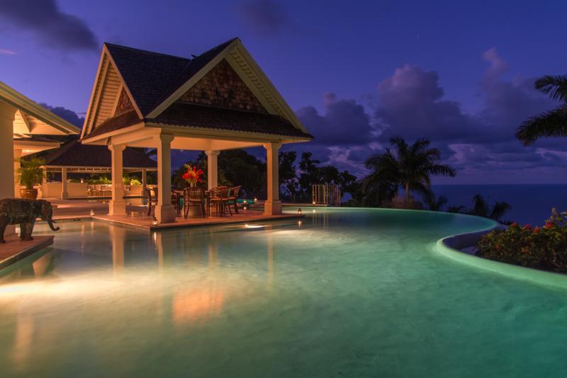 Piscina de águas Villa silenciosa com gazebo e piscina barra lateral ao entardecer