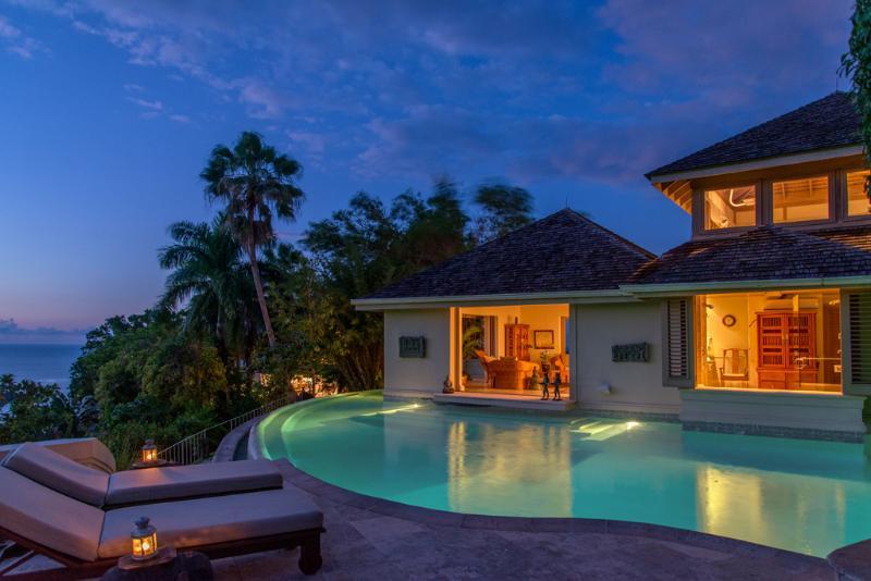 Silencioso quarto de villa de proprietários de águas Villa, casa de banho e escritório atrás da piscina ao anoitecer