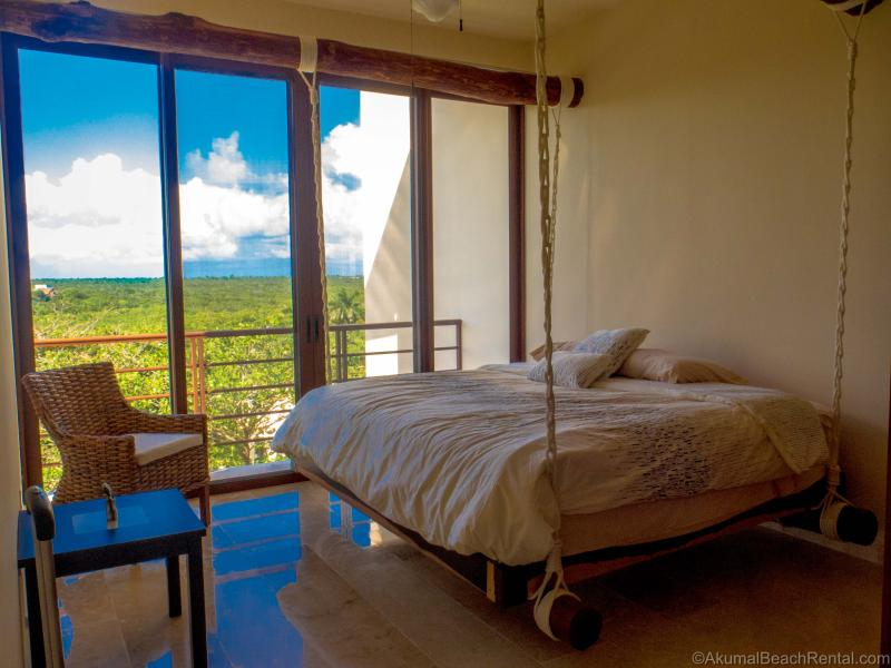 Guest BR with hanging king bed, natural vines, and 100% private jungle view