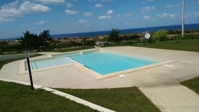 La piscina condominiale, dotata di idromassaggio e zona bimbi, e la vista del Golfo dell'Asinara