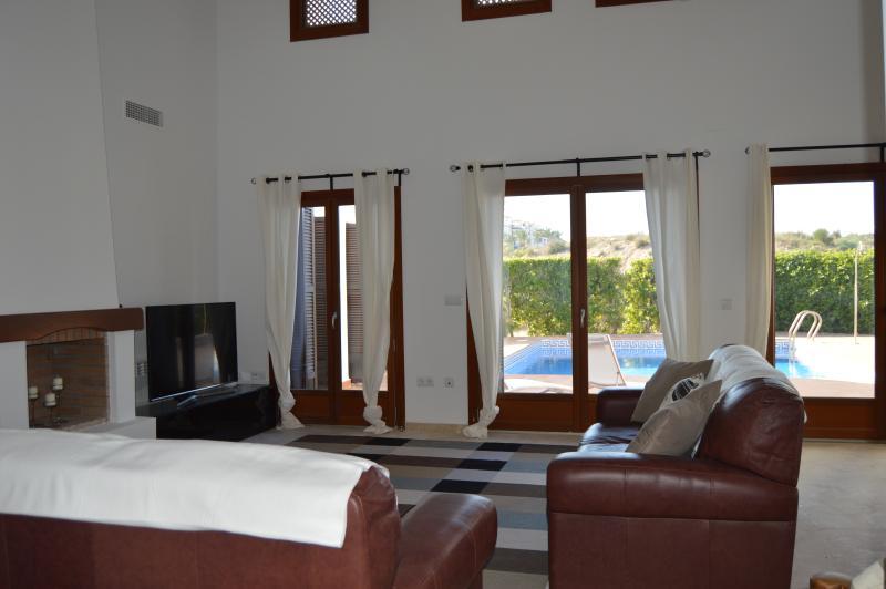 Grande sala de estar com sofás de couro confortável, com vista piscina, lareira, 55' Samsung LED TV etc.
