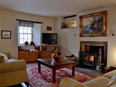 Lounge at Old Merchant House with sea views and a log burning stove