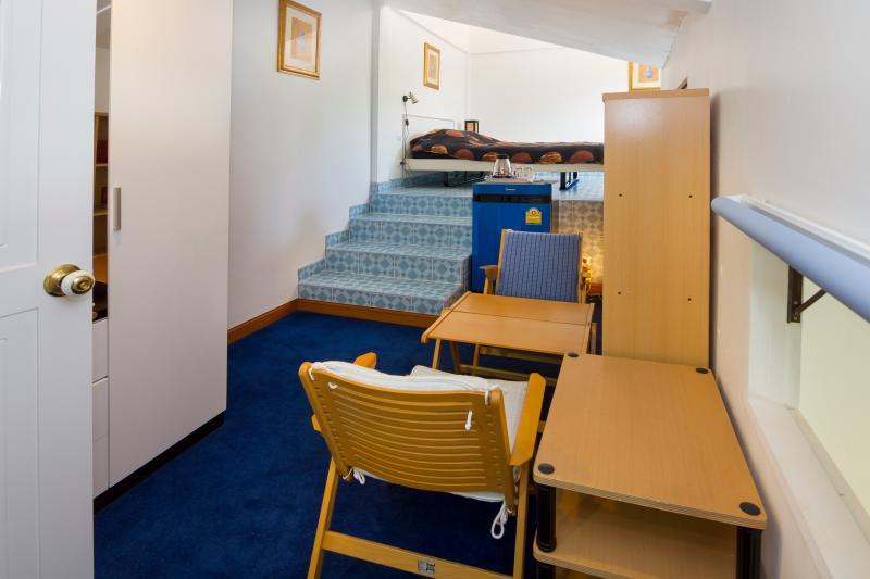 Mostra su soggiorno posto nella prima stanza della parte superiore-camera con frigorifero e grande armadio sul lato sinistro
