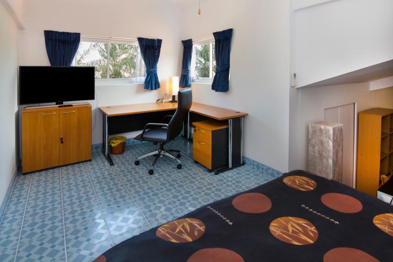 Vista su uffici a forma di L con sedia da ufficio in pelle, armadio ufficio sui rulli e 2 finestre