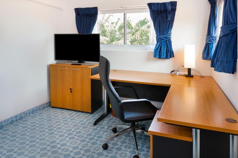Vista su ufficio a forma di L con pelle ufficio sedia e Samsung curve TV 44' con piccolo armadio