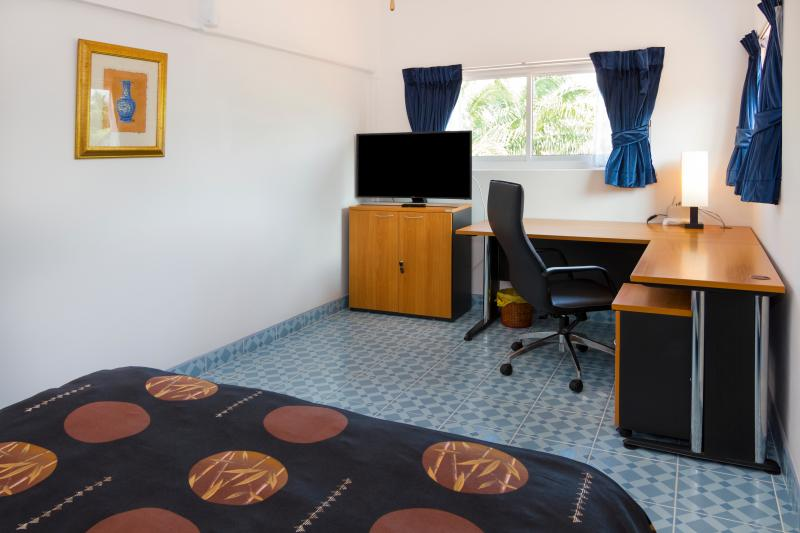 View from king size bed on L-shaped office with leather office chair and Samsung curved TV