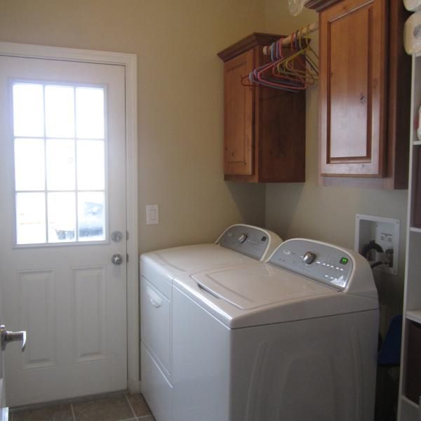 Mudroom/laundry room features Whirlpool no agitator washer and dryer and a door to the driveway