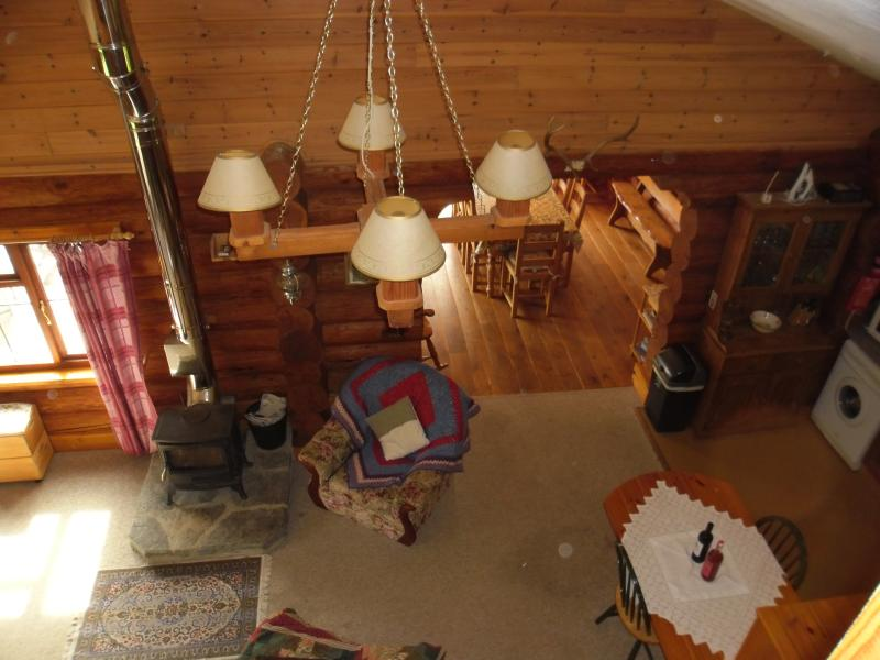 Looking down from the loft to the lounge, wood burning stove and breakfast room .