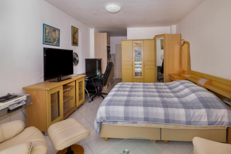 Seating place with small table, king-size bed, flat screen TV with small cupboard, office with chair