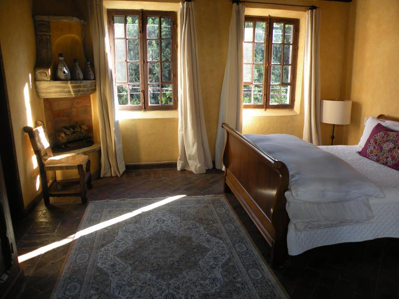 Fourth bedroom with queen and single beds, and fireplace.