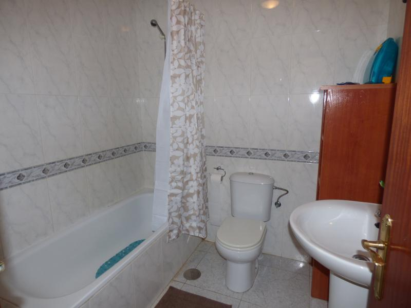 Bathroom has bath with overhead shower, toilet, wash basin with mirror above and storage shelves