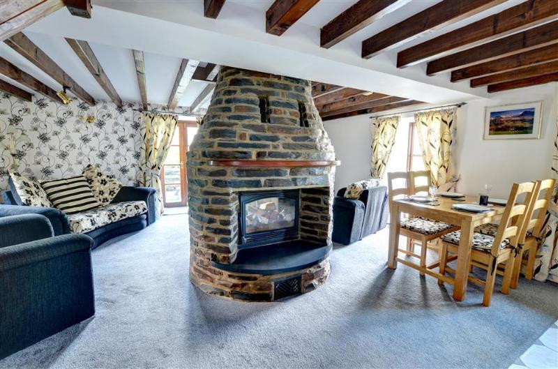 The spacious living room features a centrally placed woodburning stove in circular stone fireplace