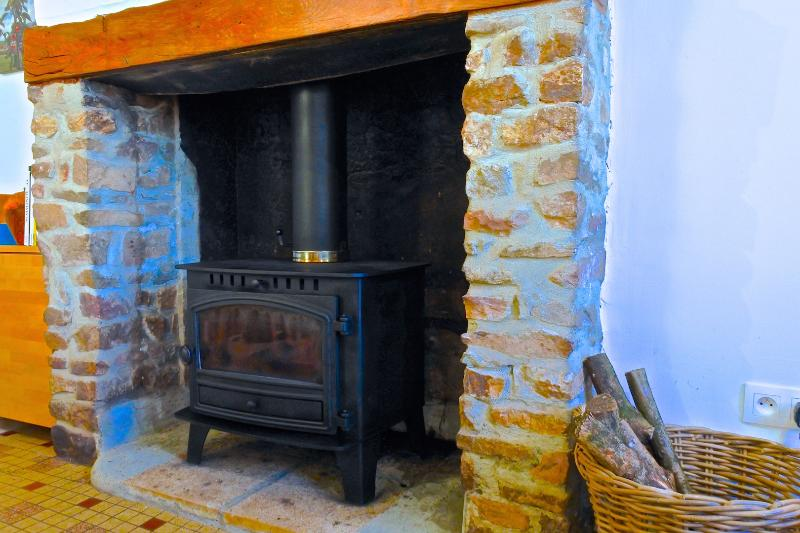 Large open fireplace with wood burning stove provides the heart of the farmhouse at L'Auberdiere.