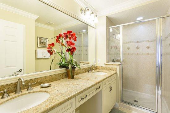 De master badkamer is voorzien van dubbele wastafels, granieten werkbladen en een inloopdouche