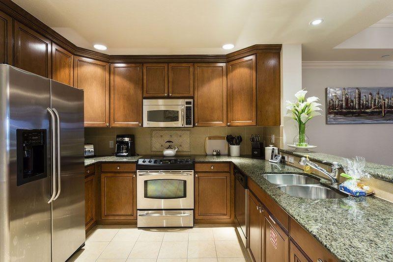 Cocina renovada con encimeras de granito y electrodomésticos de acero inoxidable
