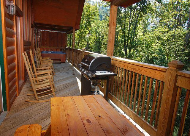Deck with picnic table, grill, porch rockers and hot tub.