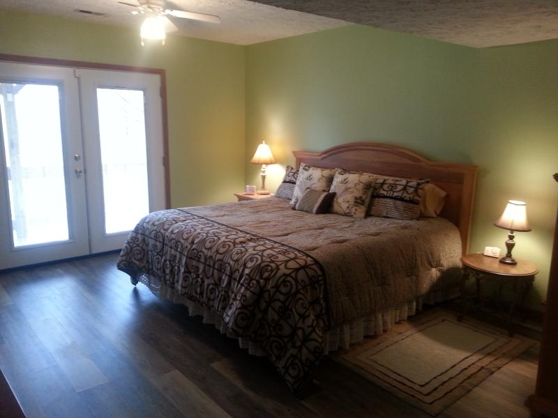 Bedroom with king size bed, bed warmer, dresser, walkin closet, and cable TV.