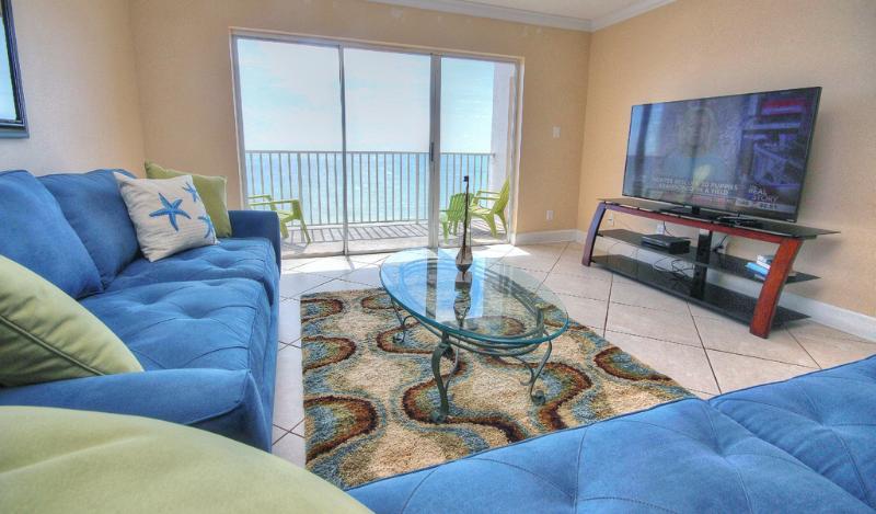 Stor platt-TV i SB702 vardagsrum och Gulf vyer från balkong
