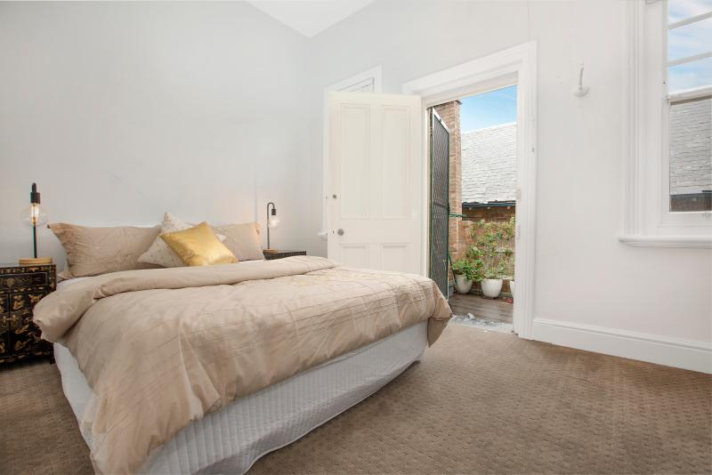 Second of 3 bedrooms, with comfortable queen bedding & backing onto private courtyard