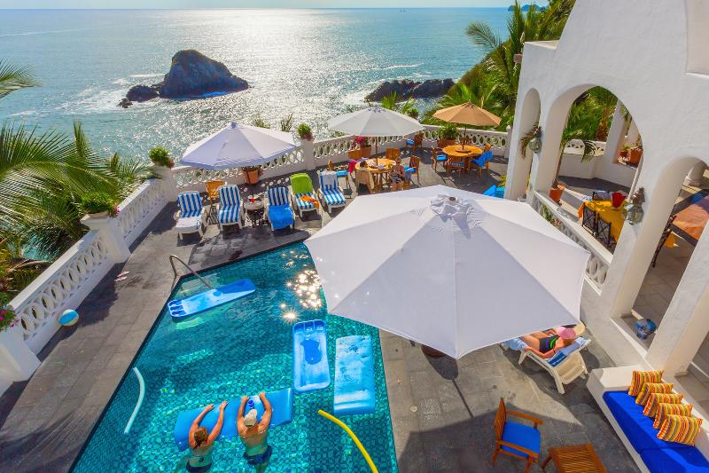 Sun drenched pool, jacuzzi, deck and pacific ocean