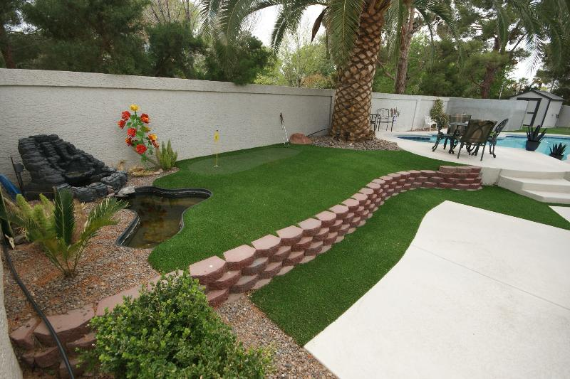Large patio with water feature & 1st or last hole green of yard course.