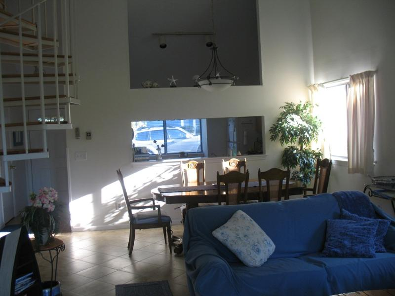 View of living and dining areas.  Clean tile floors. Cathedral ceilings.