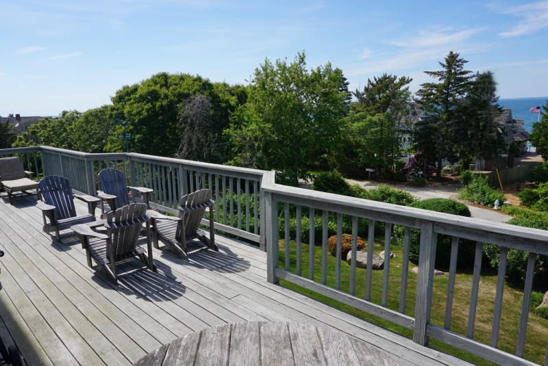 large deck with chaises, adirondack chairs, dining for eight and gas grill.